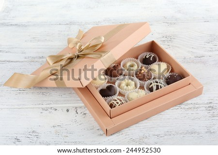 Delicious chocolate candies in gift box on table close-up - stock photo