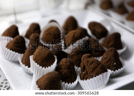 Delicious chocolate candies on plate close up - stock photo