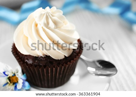 Delicious chocolate cupcake with cream on decorated wooden  table, close up