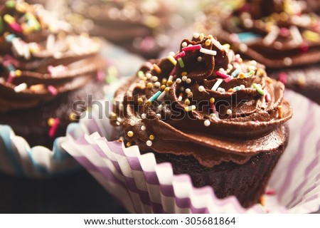 Delicious chocolate cupcakes with rich cream on the top - stock photo