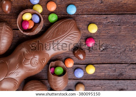 Delicious chocolate easter eggs and sweets on wooden background - stock photo