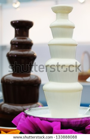 Delicious chocolate fondue fountains on a table - stock photo