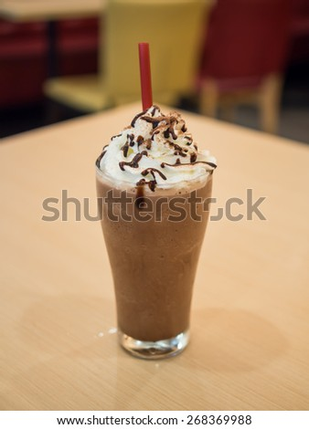 Delicious chocolate frappe with whipped cream on table - stock photo