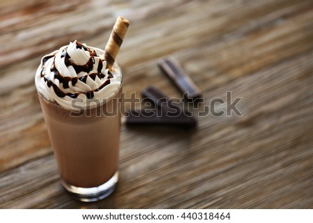 Delicious chocolate milkshake on wooden table - stock photo