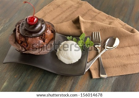 Delicious chocolate mudslide muffin with a scoop of ice cream with a cherry on top. - stock photo