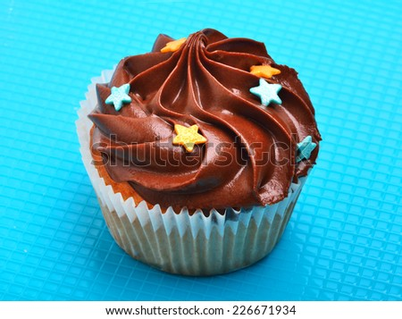 Delicious chocolate muffin on blue background - stock photo