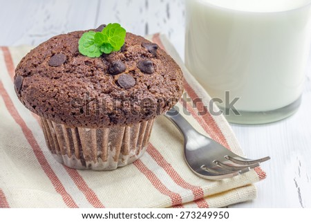 Delicious chocolate muffin with choco chips and glass of milk closeup - stock photo