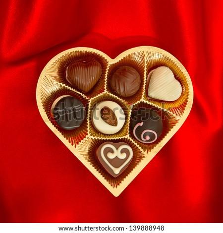 pralines sô cô la ngon trong vàng tim hộp quà hình trên nền satin đỏ
