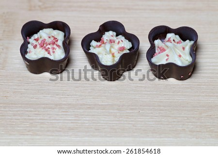 Delicious chocolate pralines on wood background - stock photo