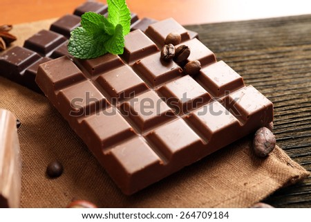 Delicious chocolates with leaves of mint on table, closeup - stock photo