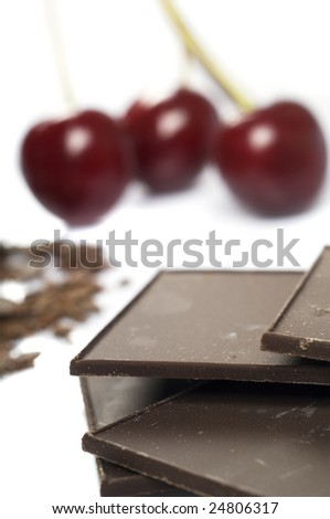 Delicious close-up of chocolate and cherry on white background - stock photo