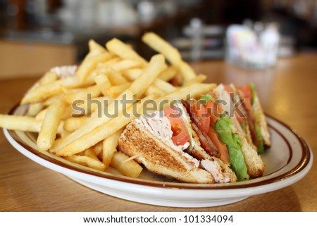 Delicious club sandwich with french fries at a diner. - stock photo
