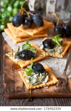 Delicious clue cheese crackers appetizer with honey and arugula on an old cooking board. - stock photo