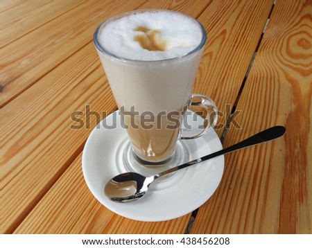 Delicious coffee latte with milk foam in a tall glass with handle.The glass stands on a white saucer on an unpainted wooden table.In the saucer lies a brilliant dessert spoon with long handle.  - stock photo