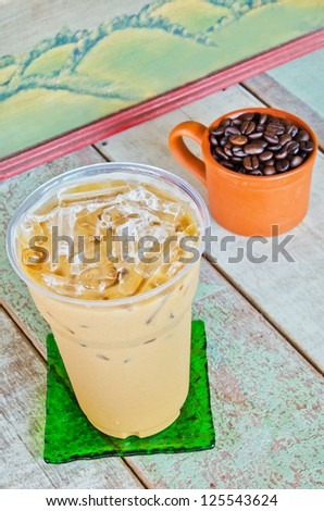 Delicious cold coffee drink with ice on wooden table - stock photo