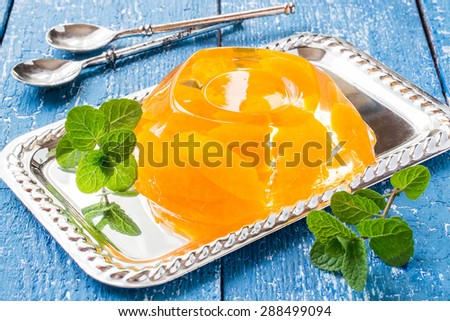 Delicious cold jelly with slices of orange and fresh mint on a mirrored metal plate, dessert spoons on blue wooden table. Selective focus - stock photo