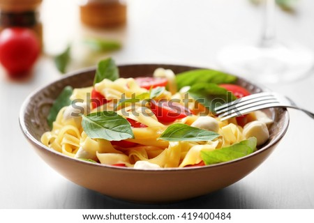 Delicious cold pasta salad in bowl on the table closeup - stock photo