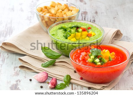 Delicious cold red and green gazpacho soup with garlic croutons in  bowls - stock photo