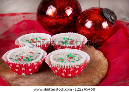 Delicious cookies and cream cheesecakes in muffin forms with red Christmas tree balls - stock photo