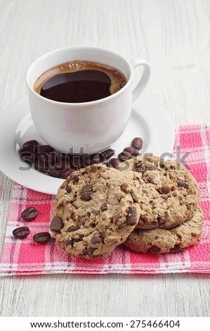Delicious cookies and cup of hot coffee on a light wooden table - stock photo