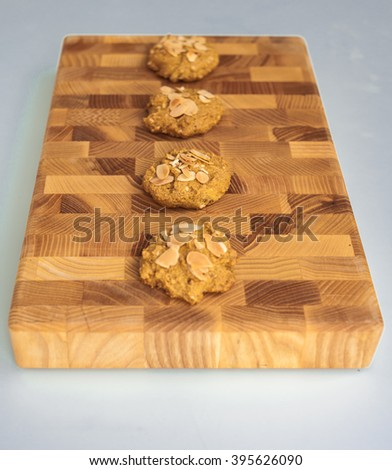 Delicious cookies with almond slices on a plate board. Corn homemade, handmade, natural.