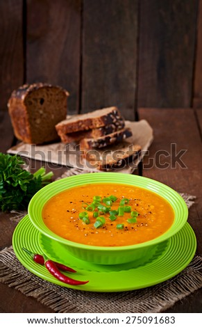 Delicious cream of pumpkin soup in green bowl on old wooden table