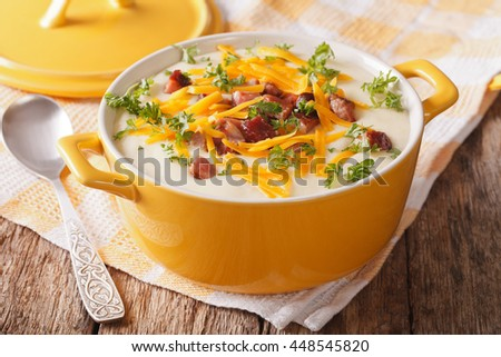 Delicious cream potato soup with bacon and cheddar cheese close-up on the table. horizontal - stock photo