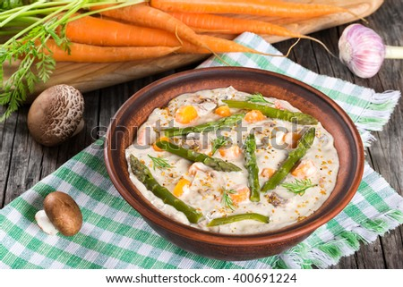 Delicious creamy cheese mushroom soup with spring carrots, asparagus and spices, decorated with dill, in a clay bowl on an old rustic table, horizontal close-up, top view - stock photo