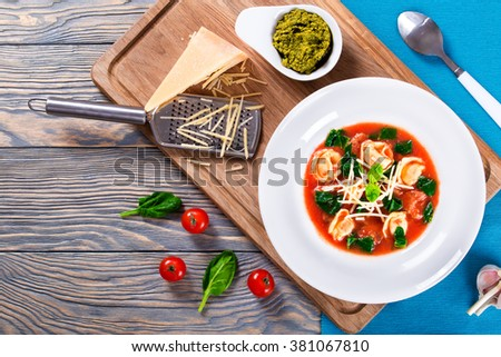 Delicious creamy tomato soup with tortellini, italian sausages, spinach, and vegetables decorated with basil leaves in a wide rim white plate on a wood table with pesto sauce in a gravy boat, top view - stock photo