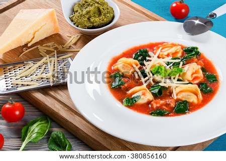 Delicious creamy tomato soup with tortellini, italian sausages, spinach decorated with basil leaves in a wide rim white plate on a cutting board with pesto sauce in a gravy boat, close-up - stock photo