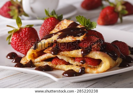 Delicious crepes with fresh strawberries and chocolate close-up on a plate. horizontal - stock photo