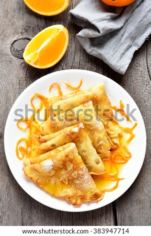 Delicious crepes with orange syrup on white plate over wooden background, top view - stock photo