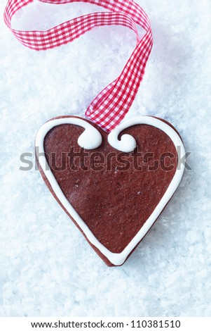 Delicious crisp freshly baked Christmas gingerbread heart with decorative icing and a festive red and white checkered ribbon on snow - stock photo
