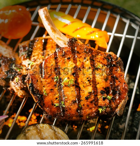 Delicious crispy barbecued marinated and seasoned pork loin cutlets with eggplant and tomato cooking on a grill , close up view of the meat - stock photo