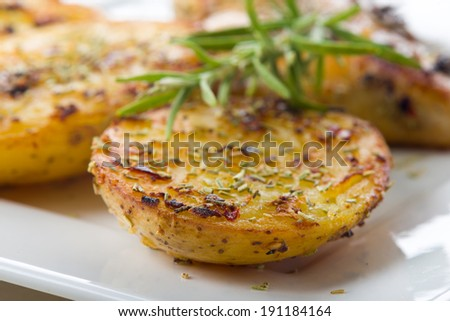 Delicious crispy savory roasted potato wedges seasoned with rosemary and served as an appetizer to a meal - stock photo