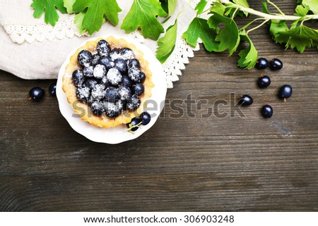 Delicious crispy tart with black currants on white stand on wooden table, top view - stock photo