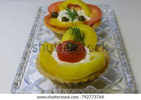 Delicious crispy tartlets with salad from cottage cheese. Crystal dish. White background.