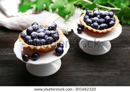 Delicious crispy tarts with black currants on white stand on wooden table, closeup - stock photo