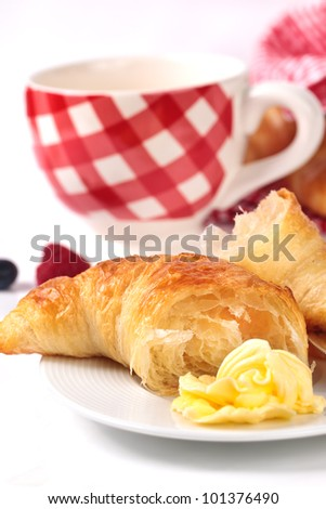 Delicious croissant with butter and coffee or tea - stock photo