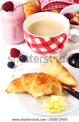 Delicious croissant with butter, jam, coffee and yogurt - stock photo