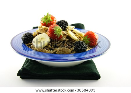 Delicious crunchy looking bran flakes and juicy fruit in a blue bowl on a black napkin on a white background