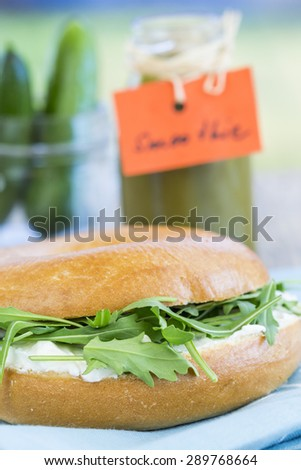Delicious crusty bagel with cream cheese and fresh arugula leaves served with a green vegetable smoothie and fresh cucumbers on a garden table - stock photo