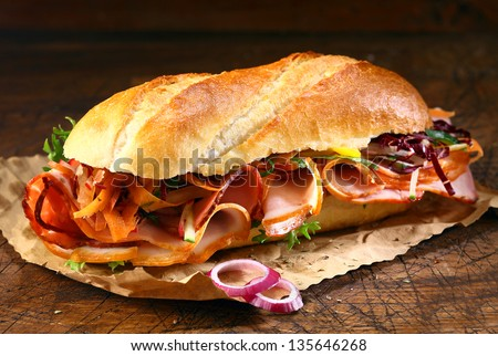 Delicious crusty baguette sandwich with ham, lettuce and onion on a small grungy crumpled sheet of brown paper on a wooden table - stock photo