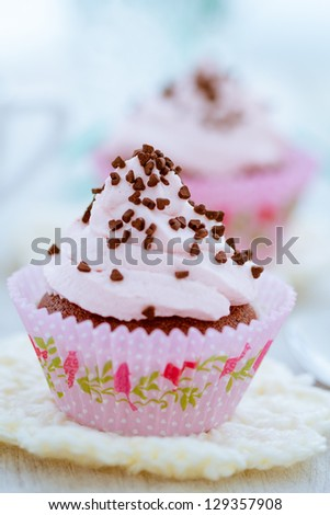 Delicious cupcake topped with buttercream and chocolate hearts. - stock photo