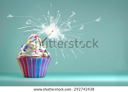 Delicious cupcake with a glittering sparkler and smarties on a whipped cream. Copy space available. - stock photo