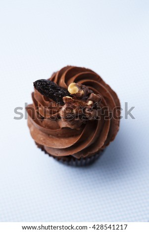 Delicious cupcake with chocolate cream on a blue background