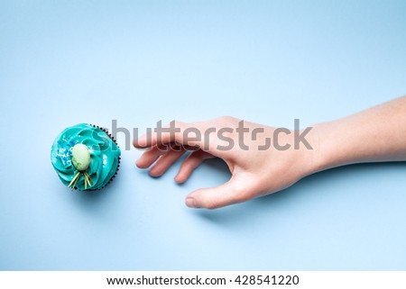 Delicious cupcake with cream and hand on a blue background - stock photo
