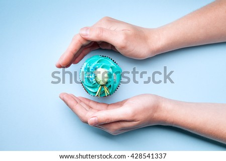 Delicious cupcake with cream in hands on a blue background