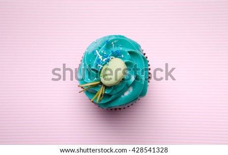 Delicious cupcake with cream on a pink background - stock photo