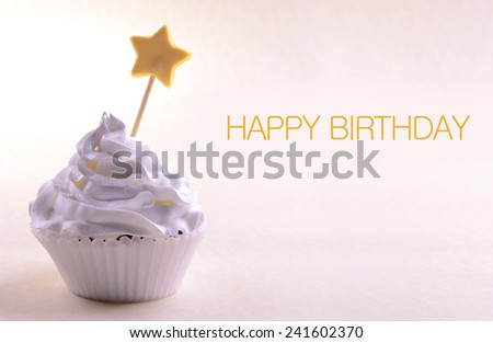 Delicious cupcake with star on stick and Happy Birthday text on light background - stock photo